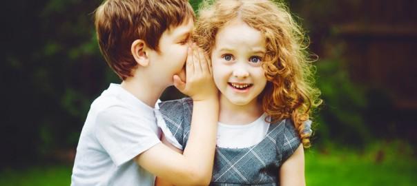 Mädchen hört einem Jungen zu.